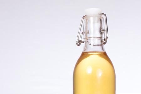 복사 공간이 금속 레버 뚜껑 및 흰색 배경 가진 투명 유리 병에서 가정 양조 맥주 닫습니다.
