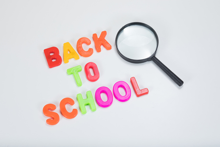 Back to school written in colourful alphabet learning letters alongside a magnifying glass with plain white background and copy space.