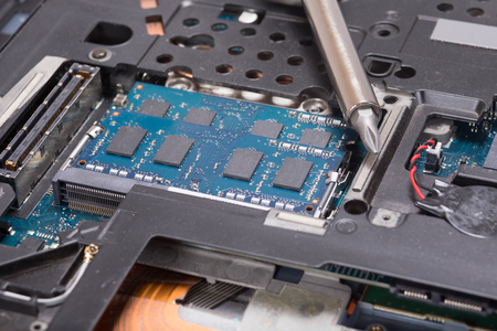 스크루 드라이버 및 전기 부품 및 유지 관리 테마 개념에서 랩톱 컴퓨터의 구성 요소 중 닫습니다.