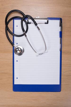 위의 의료 또는 건강 관리 개념에서 볼 나무 책상에 빈 종이 클립 보드에 거짓말하는 청진 기
