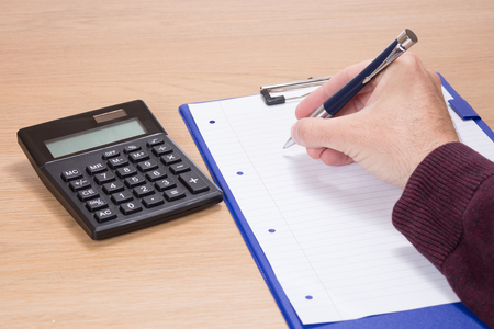Hand of a businessman holding a pen over a blank white document or page of notepaper on a clipboard with calculator alongside on a wooden desk in a conceptual image