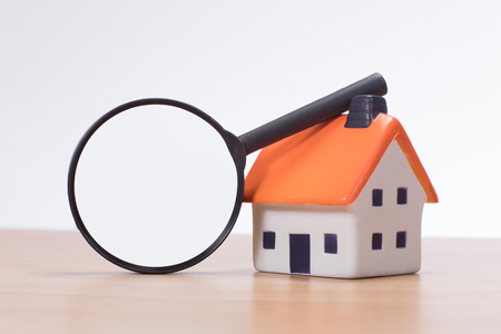Miniature of house with magnifying glass standing on desk against plain background