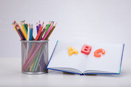 A school learning concept with colour drawing pencils an open book and ABC alphabet learning letters on a plain white background with copy space.