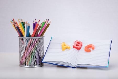 Un concepto de aprendizaje de escuela con lápices de dibujo de color un libro abierto y letras de aprendizaje de alfabeto ABC sobre un fondo blanco liso con espacio de copia.