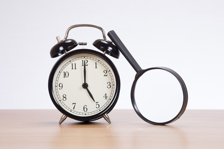 Small round magnifying glass leaning up against an old-fashioned alarm clock with bells on a wooden table with copy space on a white wall Фото со стока