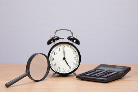 Magnifying glass, calculator and alarm clock arranged on a wooden table with copy space on a grey wall behind