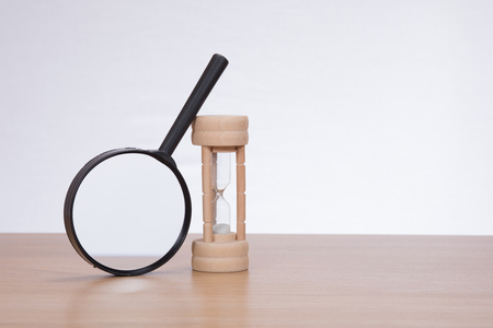 Magnifying glass leaning against sandglass on plain background