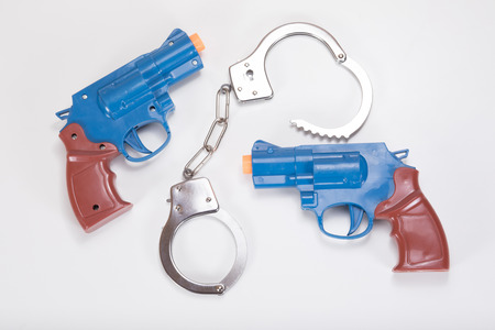 Two plastic toy handguns with handcuffs on a plain white background with copy space.