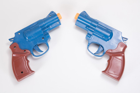 Two plastic toy handguns pointed towards each other on a plain white background with copy space.
