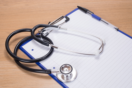 Stethoscope lying on a blank page of lined paper attached to a clipboard on a wooden desk in a conceptual medical and healthcare image Фото со стока