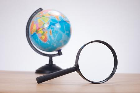여행 목적지 또는 새로운 국제 비즈니스 시장 및 기회 검색의 개념에서 나무 테이블에 돋보기와 세계 글로브 스톡 콘텐츠