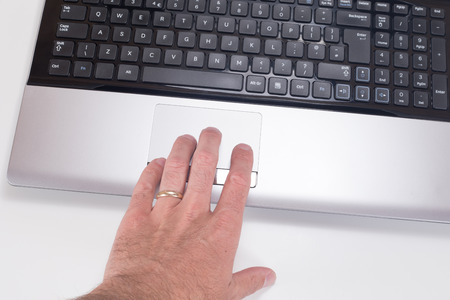 Close up of a mans hand with wedding ring using a tracking pad on a computer laptop with white background and copy space. Фото со стока