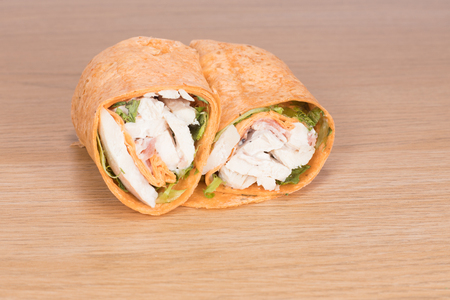 A healthy chicken salad wrap sliced in half and placed side by side on a timber table background.