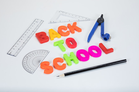 Back to school written with colourful alphabet learning letters alongside a pencil, protractor, ruler and geometry equipment on a plain white background with copy space.