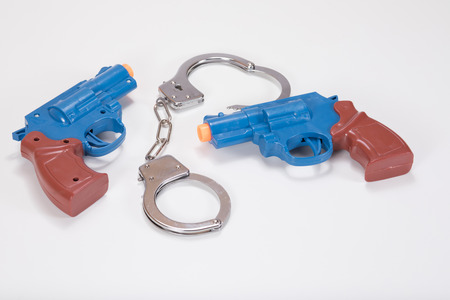 restraints: Two opposing plastic toy handguns with handcuffs on a plain white background with copy space. Stock Photo