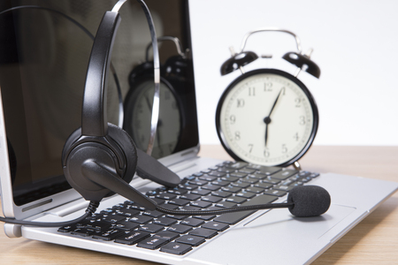 Alarm clock and headset on an open laptop computer with blank screen standing on a wooden desk n a concept of time management, deadlines and communication