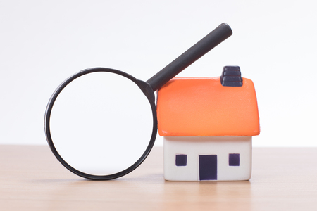 Magnifying glass leaning against house miniature on plain background
