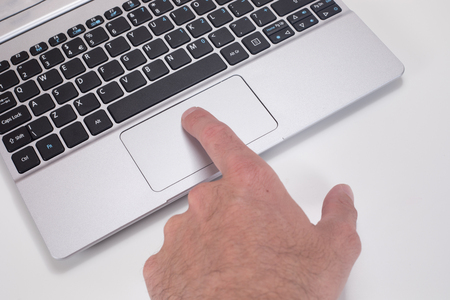 Close up of a man pressing the mouse tracking pad on a computer laptop with his finger on a white background with copy space. 免版税图像