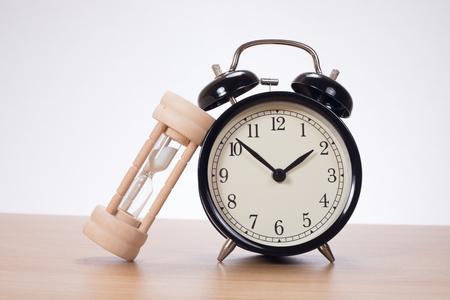 일반 배경에 알람 시계 서있는 기대어 모래 시계 스톡 콘텐츠