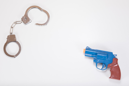 A toy plastic handgun and a set of silver handcuffs oppose each other on a plain white background with copy space. Stock Photo