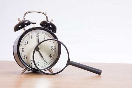 Alarm clock behind magnifying glass standing on desk against plain background Stock Photo