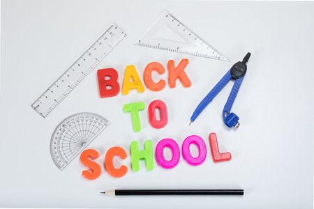 alongside: Back to school written with colourful alphabet learning letters alongside a pencil, protractor, ruler and geometry supplies on a plain white background with copy space. Stock Photo