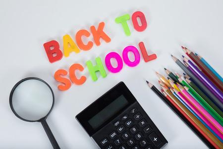 다시 돋보기, 계산기와 컬러 알파벳 복사본 공간와 일반 흰색 배경에 색깔 된 연필 작성 학교.