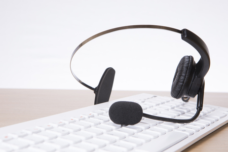 Headset with computer keyboard on desk at call centre Stock Photo