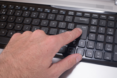 Close up of a mans finger pressing the enter button on a computer laptop keyboard.