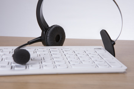 Computer keyboard with headset and mike on a wooden office desk in a concept of a call center, client services or telemarketing Stock Photo