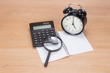 Tax deadline concept with a magnifying glass over calculator on a blank notebook with a retro alarm clock alongside on a wooden desk