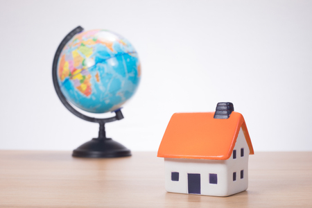 House miniature with globe in background against plain wall