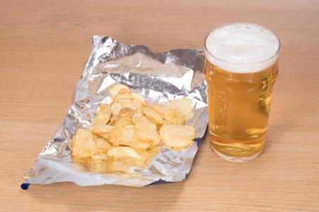 brewery: A freshly poured, frothy pint of lager beer beside an open foil packet of potato chips on a plain wooden table background. Stock Photo