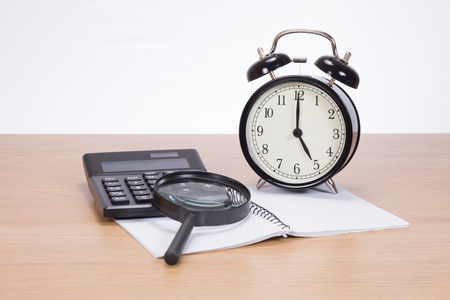 A calculator, magnifying glass, blank notebook and analogue clock on a wooden desk with white background and copy space in a finance, market research themed concept.