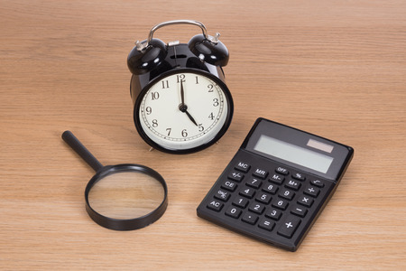 Payment deadline concept with a retro alarm clock, calculator and magnifying glass on a wooden desk viewed high angle