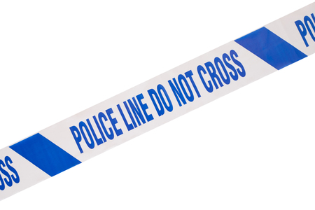 Blue, angled police line do not cross crime scene tape close up and white copy space. 免版税图像