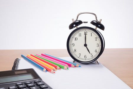 Alarm clock among colored pencils, calculator and notebook on wooden desk Фото со стока