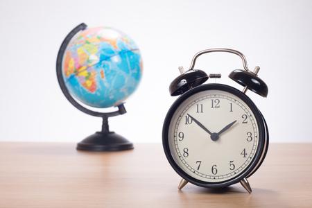 puntualidad: Alarm clock standing on desk against globe and plain background Foto de archivo
