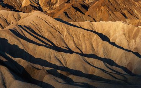 Zabriskie Point badlands at sunrise in summer, Death Valley National Park (California).