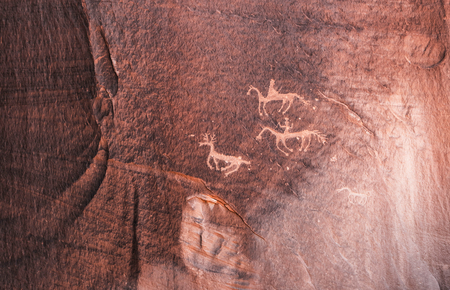 Carved Anasazi petroglyphs representing two horse riders hunting an animal related to deer - Canyon de Chelly National Monument - Arizona. Stock Photo