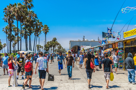 The crowded boardwalk of Venice Beach in Los Angeles during a sunny and bright day of summer.