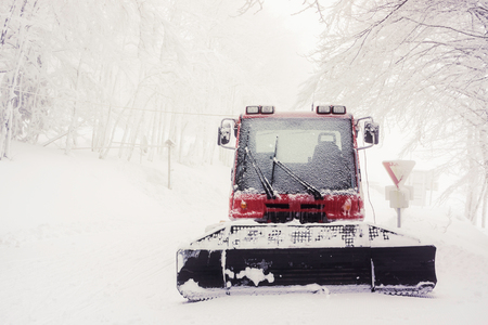 Front portrait of a snowy snow plow in winter in a foggy day with copy space - Vosges (France) - december 2017