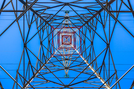 Bottom view of the metallic and symmetrical structure of a high voltage electric pylon, France.
