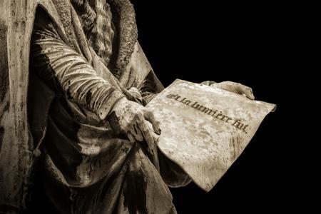 """Statue de Gutenberg tenant une page avec la phrase française """"Et la lumière fut"""" gravée dessus. Cela signifie le message biblique """"Alors il y eut une lumière"""". Isolé sur fond noir. Banque d'images"""