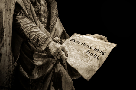 """Gutenberg statue holding a page with the biblical sentence """"Then there was light"""" carved on it. Religion concept."""