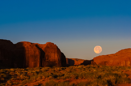 Morning landscape in Monument Valley Navajo Tribal Park with moon setting down while the rising sun is enlightening red sandstone cliffs.