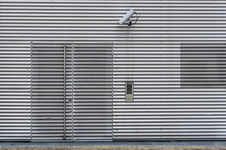 Exterior video surveillance and security system with CCTV camera on a corrugated iron wall to watch over the entrance of the building. Stok Fotoğraf