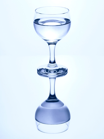 Single stemmed glass of water isolated on a white background with mirror reflection. Imagens