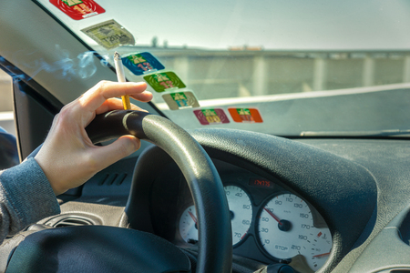 Smoking while driving a car on the highway, interior view and copy space, France.