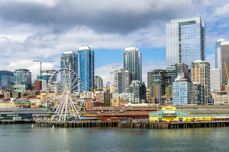 Seattle waterfront, piers 56 and 57, and skyline on a bright and cloudy day, view from the Puget Sound, Washington State, USA. Editorial